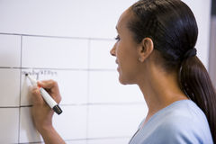 Businesswoman indoors writing on erasable board Stock Photo