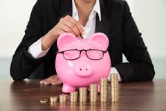 Businesswoman inserting coin in piggybank at desk Royalty Free Stock Photos