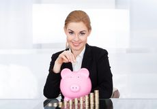 Businesswoman inserting coin in piggybank Stock Photos