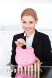 Businesswoman Inserting Coin In Piggybank Royalty Free Stock Image