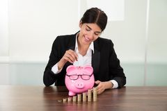 Businesswoman inserting coin in piggybank Royalty Free Stock Photography