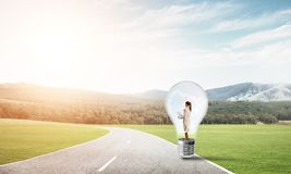 Businesswoman inside light bulb. Young businesswoman trapped inside of light bulb on asphalt road Royalty Free Stock Image