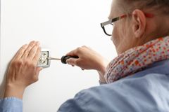 Businesswoman installing a light switch Royalty Free Stock Images