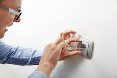 Businesswoman installing a power socket. Businesswoman installing a silver wall-mounted AC power socket with a screwdriver on a white wall, repairing an royalty free stock images