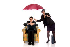 Businesswoman insurance agent. Attractive businesswoman,  insurance agent with umbrella, man in sofa.  Studio, white background Royalty Free Stock Photo