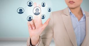 Businesswoman interacting and choosing a person from group of people icons. Digital composite of Businesswoman interacting and choosing a person from group of Stock Photo