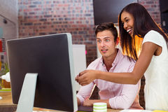 Businesswoman interacting with coworker while working on computer Royalty Free Stock Photo