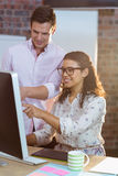 Businesswoman interacting with coworker while working on computer Stock Photography