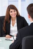 Businesswoman interviewing male candidate at desk Royalty Free Stock Photography