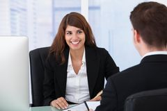 Businesswoman interviewing male candidate at desk Royalty Free Stock Photos