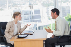 Businesswoman interviewing a smiling businessman Royalty Free Stock Photo