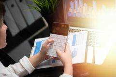 Businesswoman investment consultant analyzing company annual financial report balance sheet statement working with stock photo