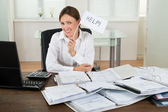 Businesswoman With Invoices Asking For Help. Young Businesswoman With Invoices Asking For Help At Desk Stock Image