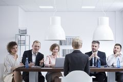 Businesswoman during job interview. Elegant businesswoman during a job interview with a group of recruiters in corporation stock photos