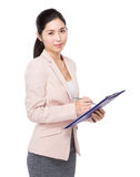 Businesswoman jot note on clipboard Royalty Free Stock Photography
