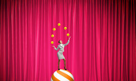 Businesswoman juggling with balls Stock Photography