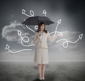 Businesswoman with jumbled arrows holding umbrella Royalty Free Stock Photos
