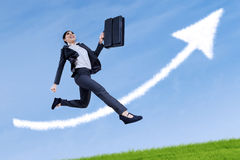 Businesswoman jumping with arrow sign. Happy asian businesswoman running and jumping with arrow sign Royalty Free Stock Photos