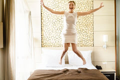 Businesswoman jumping on bed in hotel room. Royalty Free Stock Images