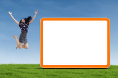 Businesswoman jumping with blank board. Happy businesswoman is jumping with blank board on the green grass Royalty Free Stock Photos