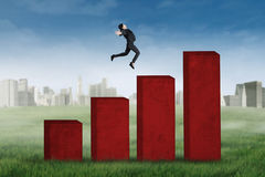 Businesswoman jumping on business chart Stock Photography