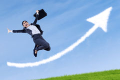 Businesswoman jumping and holding a briefcase. Excited asian businesswoman jumping and holding a briefcase with arrow sign Stock Photos