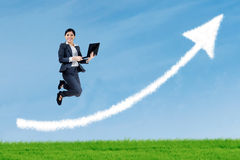 Businesswoman jumping and holding a laptop Stock Photo