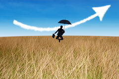 Businesswoman jumping holding umbrella in field Royalty Free Stock Photo