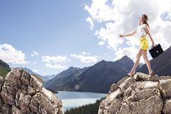 Businesswoman jumping on mountains. Stock Image