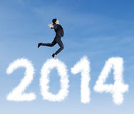 Businesswoman jumping over clouds of 2014. Happy asian businesswoman is jumping over clouds of 2014 Royalty Free Stock Photo