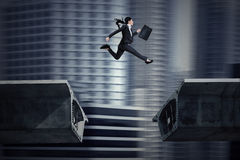 Businesswoman jumping over a gap in the bridge. Young asian businesswoman with briefcase jumping over a gap in the bridge Royalty Free Stock Photo