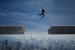 Businesswoman jumping over a gap in the bridge. Young businesswoman jumping over a gap in the bridge over cityscape Royalty Free Stock Image