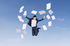 Businesswoman jumping with papers. Asian businesswoman jumping and throwing papers into air in the blue sky Royalty Free Stock Photography