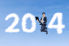 Businesswoman jumping on shaped clouds of 2014 Royalty Free Stock Image