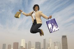 Businesswoman Jumping With Shopping Bags. Portrait of a cheerful senior businesswoman jumping in midair with shopping bags Stock Photos