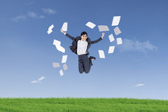 Businesswoman jumping and throwing papers. Asian businesswoman jumping and throwing papers into air in the green field Royalty Free Stock Photo