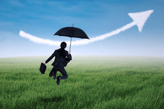 Businesswoman jumping with umbrella Stock Photography