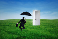 Businesswoman jumps in front of opportunity door Royalty Free Stock Image