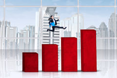 Businesswoman jumps over business chart Stock Photo