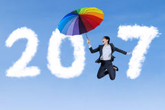 Businesswoman jumps with umbrella and 2017 Stock Images