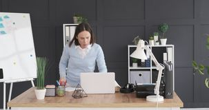 Businesswoman keeping file on shelf and using laptop at office desk. Businesswoman keeping file on shelf and returning to her desk to check mail stock video footage