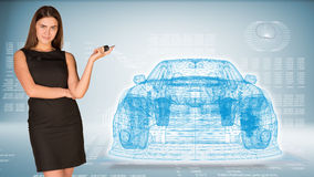 Businesswoman with key and wire frame car Stock Photos