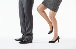 Businesswoman kicking a businessman Royalty Free Stock Photos