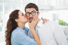 Businesswoman kissing her handsome colleague Stock Photography