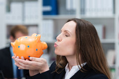 Businesswoman kissing her piggy bank Stock Images