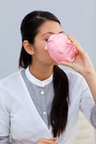 Businesswoman kissing a piggybank Stock Photos