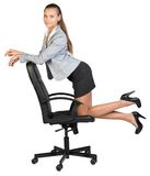 Businesswoman kneeling on office chair, looking at Royalty Free Stock Photography