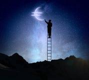 Businesswoman on ladder reaching moon Royalty Free Stock Photos