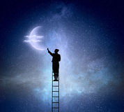 Businesswoman on ladder reaching moon Royalty Free Stock Photography