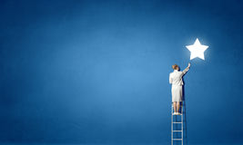 Businesswoman on ladder reaching star Stock Photography